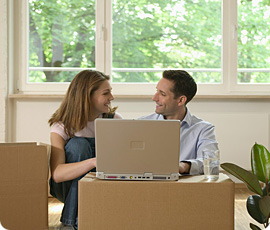 Smiling couple working on laptop among moving boxes.